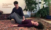 Jay Reiss practicing Breema bodywork with a woman on the floor
