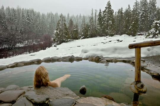 Woman soaking in the snowy cascades at Breitenbush Hotsprings Retreat Center Oregon
